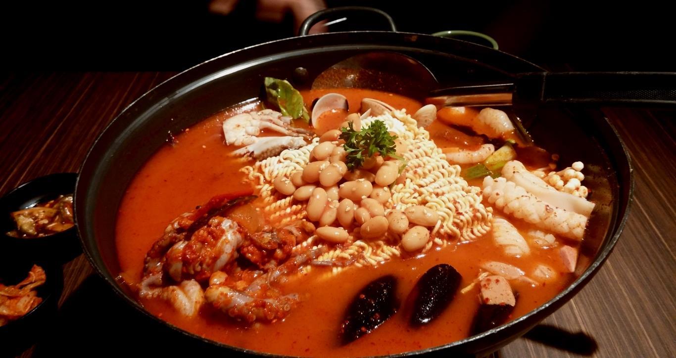 Món ăn này ra đời vào thế kỷ 20 trong thời kỳ chiến tranh Hàn Quốc. Tận dụng những loại thịt đóng hộp cung cấp bởi Mỹ, người Hàn Quốc đã sáng tạo ra món ăn cay nóng, dùng kèm với các món đặc trưng của Hàn Quốc như kimchi, rong biển. Từ một món ăn đơn giản ra đời trong thời chiến, Army Stew đã trở nên nổi tiếng trên toàn đất nước.