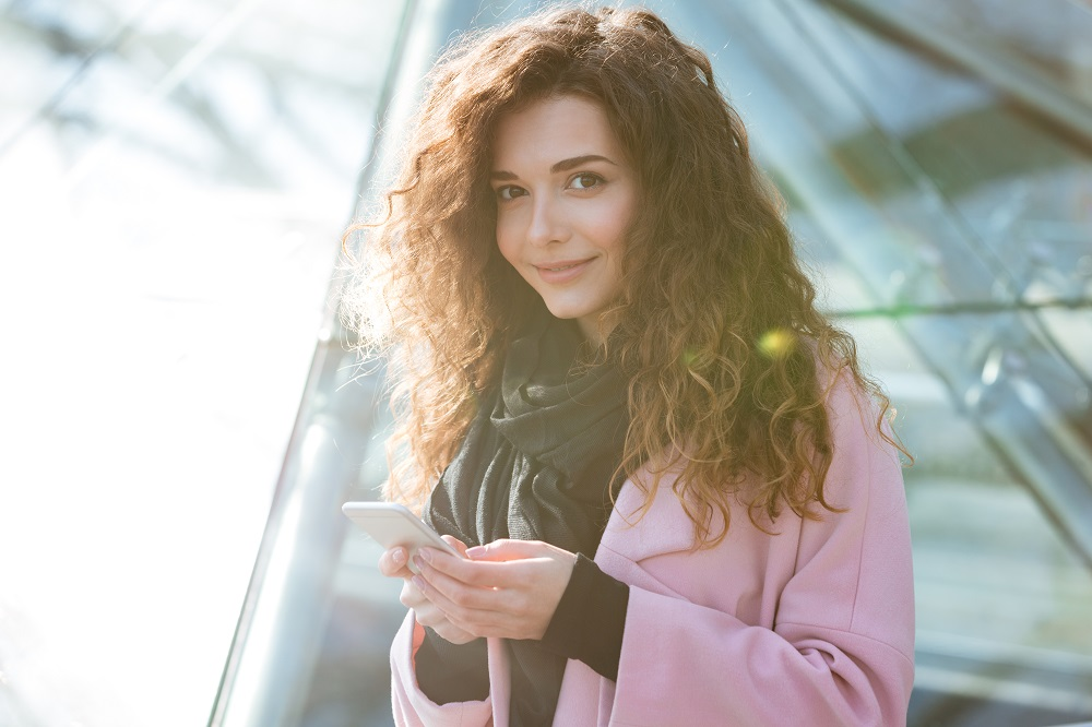 young-woman-using-her-phone-in-the-sunny-city-P99HCMA-1.jpg